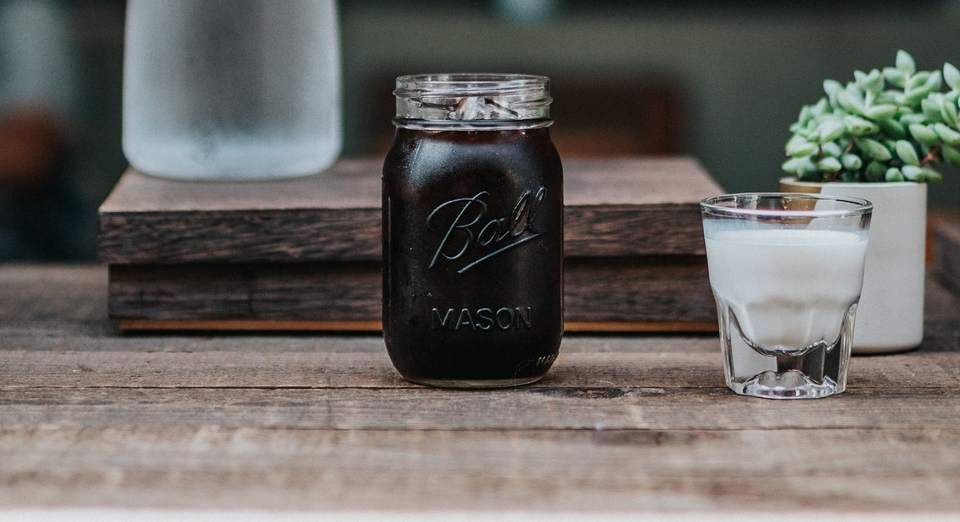 clear mason jar on brown surface with cold brew coffee and creamer