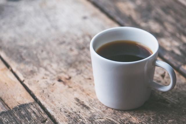 coffee filled white ceramic mug on brown wooden surface